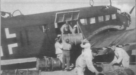 """Наземный персонал загружает в кабину самолета Ju-52/3m g5e бочки с горючем, предназначенным для корпуса """"Африка"""". аэродром на Сицилии. Самолеты Ju-52/3m g4e и Ju-52/3m g4e имели небольшое дополнительное окно в борту фюзеляжа за грузовой дверью. В проеме этого окна мог устанавливаться 7,92-мм пулемет MG-15."""