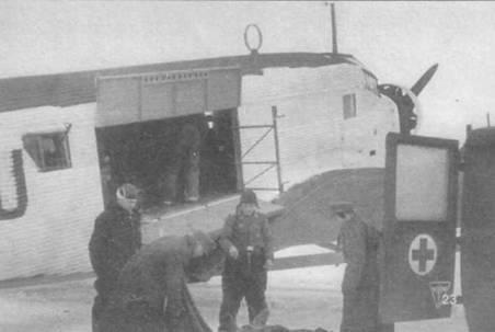 Погрузка раненых в кабину Ju-52/3m g7e. На этой модели трехмоторного Юнкерса в правом борту имелись большая двустворчатая грузовая дверь. Обратите внимание — три передних окна в борту фюзеляжа закрашены белой краской. На Ju-52/3m g7e опять появилась передняя дверца в правом борту фюзеляжа, которая была на Ju-52/3m g3e, но отсутствовала на Ju-52/3m g4e. В проеме последнего окна установлен пулемет MG-1S.