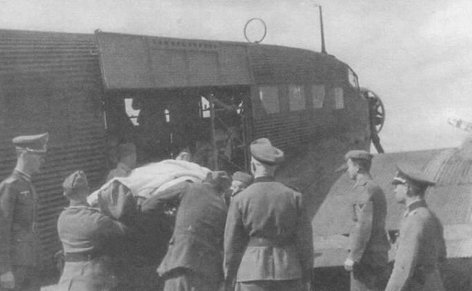 Офицер вермахта наблюдает за погрузкой раненых солдат в кабину самолета Ju-52/3m g7e. Верхняя створка грузового люка зафиксирована в открытом положении. Ju-52/3m мог перевозить до 12 раненых на носилках и одного медицинского работника.