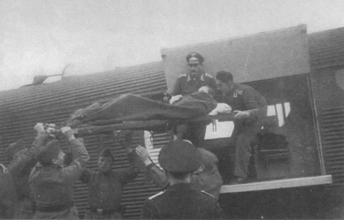 Летчики помогают солдата. и выгрузить из кабины самолета Ju-52/3m g 10е раненого на носилках. Ни борта фюзеляжа вместо обычных опознавательных знаков нанесен красный крест в белом круге.