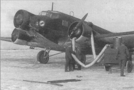 Техники обогревают перед запуском левый двигатель Ju-52/3m, Восточный фронт. Два других мотора уже прогреты и запущены. В России зимой <a href='https://ours-nature.ru/b/book/11/page/6-5-vozdushnaya-obolochka-zemli/51-32-temperatura-vozduha' target='_blank' rel='external'>температура воздуха</a> -5 град. С — не редкость. Двигатели BMW-132L на таком морозе не запускались, их предварительно требовалось прогревать от внешнего источника. Самолет имеет по два маслорадиатора на каждый двигатель — стандартный вариант.
