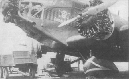 Техническое обслуживание самолета Ju-52/3m g3e в перерыве между боевыми вылетами. Эта машина имеет по три маслорадиатора под каждым двигателем, вместо двух как обычно. Обратите внимание на изображение черепа с костями и надпись «Zaragosa», видимо самолет принимал участие в налете бомбардировщиков из К/88 на Сарагосу. Стойки основных опор шасси и обтекатели колес — черный, на обтекателях нарисованы белые полосы.