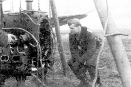 Кавалер Рыцарского креста с дубовыми листьями гауптман Курт Брандль с интересом наблюдает за сменой мотора на одном из истребителей подчиненной ему II./JG-3.