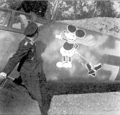 А здесь Мики Маус — уже большой! К тому же у мышонка появилась запасная пара башмаков, как напоминание о вынужденной посадке Караганико летом 1943г., после которой он добирался на аэродром на своих двоих. По стеклению фонаря кабины лазает шотландский терьер — любимец майора. Эта псина послужила прототипом эмблемы 1./JG-77, когда стаффелем командовал Карганико. Майор Карганико погиб на десятый день после вторжения союзников во Францию.