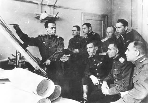 М.Т. Калашников докладывает офицерам отдела изобретений Главного Артиллерийского Управления Министерства Вооруженных Сил СССР о конструктивных особенностях автомата АК (1949г.).