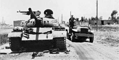 Израильские солдаты проезжают мимо сирийского танка Т-54-3, подбитого в ходе боев на Голанских высотах. 1967 год.