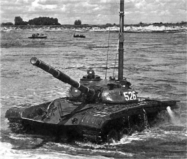 Танк Т-72 с установленной воздухопитающей трубой выходит из воды после преодоления водной преграды.