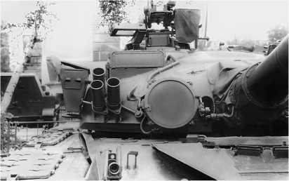 Башня танка Т-80Б спереди слева. Хорошо видны ИК-осветитель Л-4А, дымовые гранатометы, антенный блок ГТН-12 КУБ «Кобра» и амбразура спаренного пулемета ПКТ.