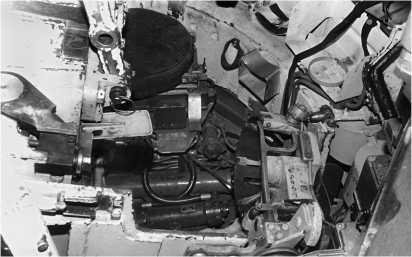 Элементы механизма подачи механизма заряжания танка Т-80Б. Слева — казенник пушки, внизу — левое ограждение пушки с установленным на нем механизмом улавливания экстрактированного поддона, вверху — сиденье командира танка.