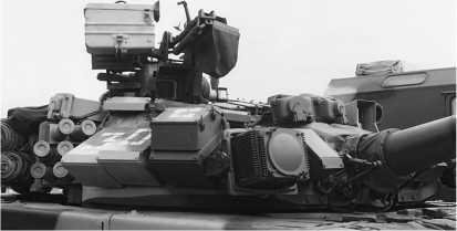 Башня Т-90 крупным планом. Над стволом пушки установлены приемные головки обнаружения лазерного излучения, а справа от пушки — правый осветитель системы оптико-электронного подавления «Штора-1».