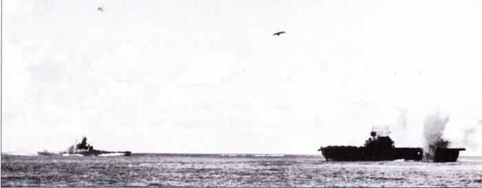 «Южная Дакоты» в бою, Санта-Круз, 26 октября 1942г. Бомба подняла столб воды рядом с бортом авианосца «Энтерпрайз». Сбросивший бомбу японский самолет «Вэл» (Аичи D3A2 тип 99 модель 12) падает, объятый пламенем. Это один из 26 сбитых в тот день зенитчиками линкора японских самолетов. «Южная Дакота» получила прямое попадание бомбы в башню главного калибра «В», но башенная броня пробита не была. Взрывом бомбы было ранено несколько человек, находившихся на мостике линкора, включая командира корабля. Линкор продолжил бой.