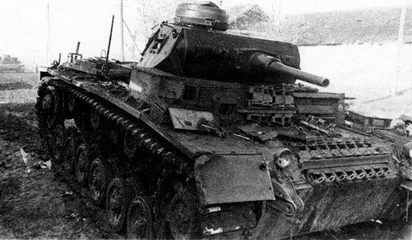 Этот Pz.III из 13-й танковой дивизии вермахта, подбитый на Северном Кавказе в районе Орджоникидзе осенью 1942 года,— характерный пример «промежуточной модификации», которые порой возникали в процессе модернизаций и ремонтов. Судя по ходовой части и корпусу, эта машина — модификации F, однако башня — от Ausf.H или G поздних выпусков.