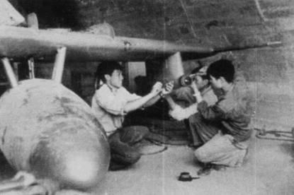 Техники монтируют на пилоне под крылом истребителя МиГ-17 какое-то хитрое устройство. По блеску линзы можно предположить, что устройство является разведывательной фото- или кинокамерой. Самолет находится в бетонном укрытии, сделанном в естественной пещере. К таким хорошо замаскированным ангарам истребители доставляли на внешней подвеске тяжелые вертлеты Ми-6, а внутрь самолеты затаскивали грузовые автомобили.