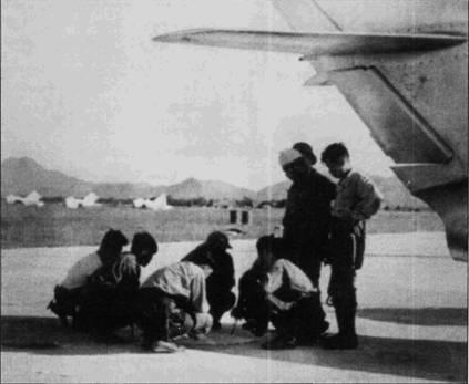 Летчики ВВС ДРВ в тени истребителя МиГ-17 обсуждают боевой вылет, аэродром Нойбай, 1965г. На заднем плане видны накрытые чехлами истребители МиГ-17.