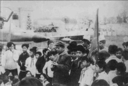 Полковник Нгуен Ньят Чиеу рассказывает школьником на аэродроме Бачмаи о воздушных боях. Фоном беседы служат два музейных экспоната — трофейный истребитель F-5E и ветеран воздушной войны над Вьетнамом самолет МиГ-17 Ф.