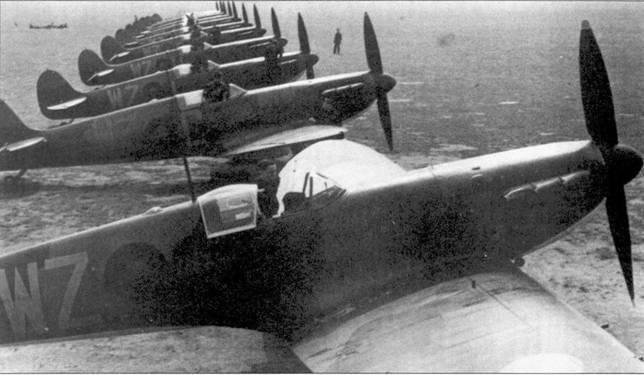 Линия истребителей «Спитфайр» самого первого выпуски. Снимок сделан на презентации новых машин, поступивших на вооружение 19-й эскадрильи, Даксфорд, 4 мая 1939г. Все 11 «Спитфайров» оснащены двухлопастными деревянными воздушными винтами, узкими мачтами радиоантенн, в фонаре кабин отсутствуют лобовые бронестекла. Обратите внимание на кольцевые прицелы, установленные под прозрачными козырьками фонарей. На втором истребителе хорошо видна плоская, без каплевидного выступа, как на первой машине, сдвижная часть фонаря кабины. Ближайший самолет — единственный, на котором отсутствует индивидуальная литера, на фюзеляже нанесен лишь код эскадрильи — «WZ».
