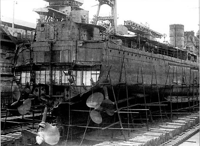 Легкий крейсер «Натори» в сухом доке военно-морской базы Зелетан (Сингапур), 5 февраля 1943г… Корабль завели в док для ремонта боевых повреждений — американская субмарина «Тэутог» всадила 9 января 1943г. в крейсер две торпеды, взрывами которых у корабля оторвало кормовую оконечность корпуса.
