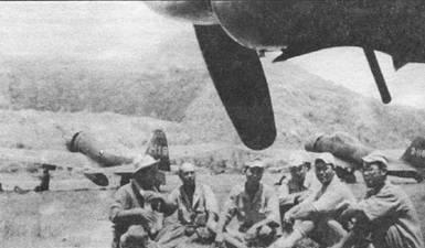 Техники отдыхают у истребителя «Зеро», Рабаул. Один техник держит в руках бутыль с саю.