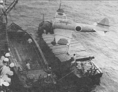 Перегрузка истребителя A6M21 с баржи на транспорт, законцовки крыла самолета сложены. Фюзеляжный опознавательный знак «хиномару» имеет белую окантовку, что редко встречаюсь на полностью серых «зеро».