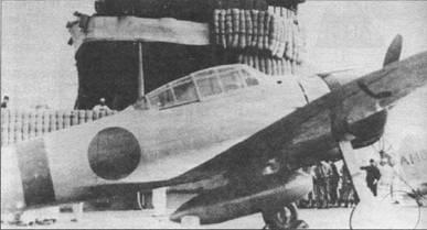 Истребитель A6M2 модель 21 на палубе авианосца «Акаги». Корабли находится недалеко от Гавайских островов. Вокруг фюзеляжа «Зеро» нанесена полоса красного цвета. На киле (на снимке не видна) – код «A1-105» черного цвета. Выше и ниже кода – полосы желто-оранжевого цвета. На заднем плане – вертикальное оперение «Зеро» с кодом «А1-101» – самолет командира 1-й коку сентай майора Сигеру Итая.