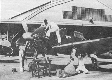 Техническое обслуживание «Зеро» модель 21 из Оита кокутай. Техники возятся с двигателем Сакаэ-12. Бортовой код самолета «О-ТА-III» нанесен на нижнюю поверхность крыли, что необычно для тренировочных самолетов.