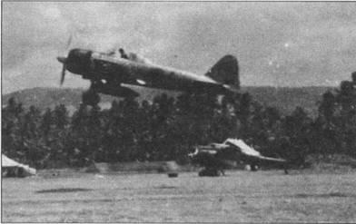 Q-122, «Зеро» модель 32 взлетает с аэродрома Рабаул-Восток. По голубой полосе на фюзеляже можно определить, что это самолет командира звена. Радиооборудование с истребителя снято – нет радиомачты. Ни заднем плане видно двухмоторный разведчик Накаяма JINI-R тип 2.