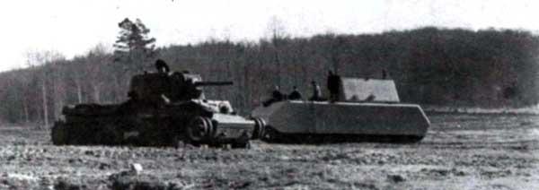 «Маус» проезжает мимо расстрелянного советского тяжелого танка КВ-1. Бёблинген, зима 1944 года. Появление КВ на поля боя летом 1941 года стало катализатором процесса создания новых немецких тяжелых и сверхтяжелых танков