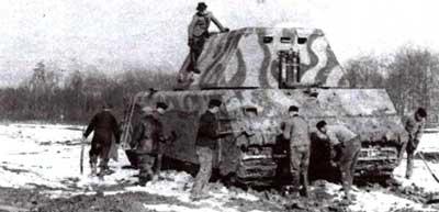 ЧП во время испытаний «Мауса» в Бёблингене. 16 марта 1944 года, при попытке преодолеть вязкий участок грунта многотонная махина безнадежно застряла. Спасательная операция с привлечением личного состава 7-го запасного <a href='https://arsenal-info.ru/b/book/348132256/10' target='_self'>танкового батальона</a> завершилась успешно, после чего танк еще долго очищали от грязи. На фото в центре хорошо видны серп и молот, изображенные на борту танка