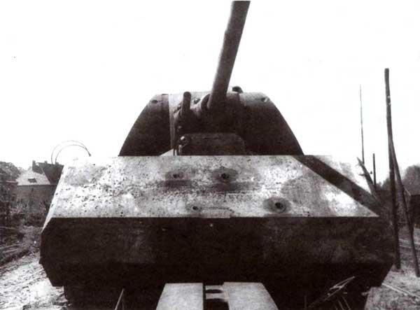 «Маус» на платформе перед отправкой в СССР (фото сверху и внизу). В лобовой броне корпуса хорошо видны вмятины от снарядов, что позволяет утверждать, что немцы проводили испытания первого прототипа обстрелом. Возможно, впрочем, что это следы от советских снарядов. Обращает на себя внимание массивная литая крышка люка для загрузки боеприпасов в кормовом листе башни. Хорошо различимы шиповые соединения кормового и бортовых листов и штифты