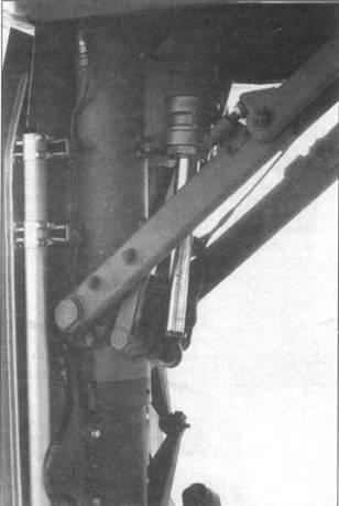 Два снимка. Верхняя часть передней стойки шасси, вид сзади и слева. На одном из снимков заметен крюк, фиксирующий стойку в убранном положении.