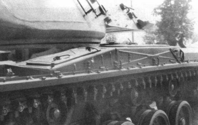 Кронштейн крепления пушки в положении по-походному (в центре). Ящики для ЗИП и снаряжения на надгусеничной полке (слева)
