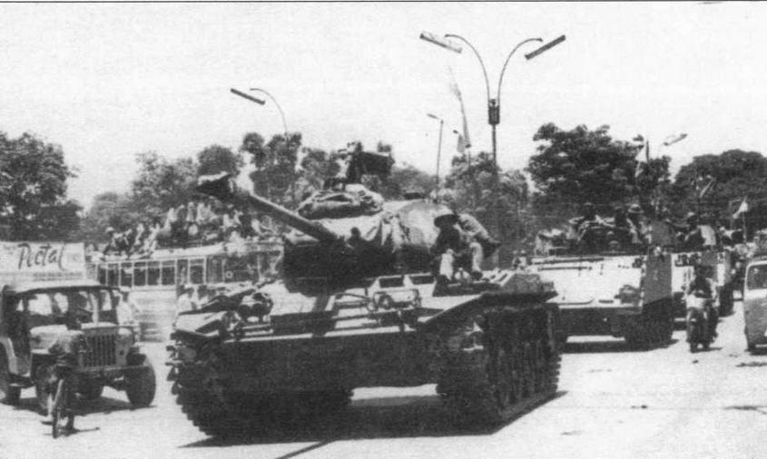 Колонна войск Народного фронта освобождения на трофейных американских бронетранспортерах М113, возглавляемая трофейным танком М41, движется по улицам Сайгона. 30 апреля 1975 года