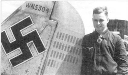 Майор Йоханнес Зейферт, пока еще в звании гауптмана, позирует на фоне руля направления своего истребителя, лето 1942г. Зейферт командовал I./JG-26 с июля 194/ г. по май 1943г. В сентябре 1943г. Зейферт стал командиром II группы. Через два месяца он погиб, столкнувшись в горячке воздушного боя с «Лайтнингом». Йоханнес Зейферт сбил 57 самолетов, в том числе 11 — в период короткой командировки I./JG-26 на Восточный фронт.