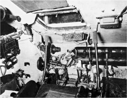 Отделение управления танка Т-34. Место механика-водителя. Черный цилиндр слева вверху — уравновешивающий механизм крышки люка. Справа от люка, над баллонами со сжатым воздухом — аппарат ТПУ.