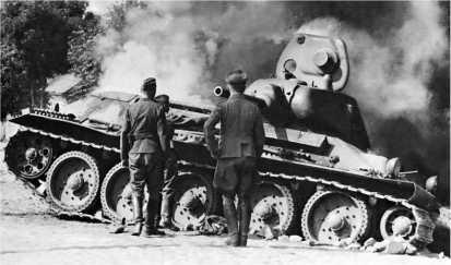 Немецкие солдаты осматривают подбитый танк Т-34. Лето 1941 года. Эта машина оснащена литой башней, что было редкостью — большая часть «тридцатьчетверок» довоенного выпуска, тем более ранних, с пушкой Л-11, имела сварные башни.