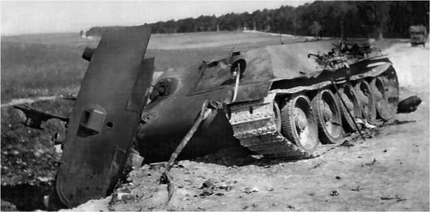 Подбитая «тридцатьчетверка» самых ранних выпусков, о чем говорит сплошная гнутая лобовая деталь корпуса. В кормовой части крыши башни хорошо виден стакан антенного ввода, что также было характерно для первых серийных машин. Лето 1941 года.