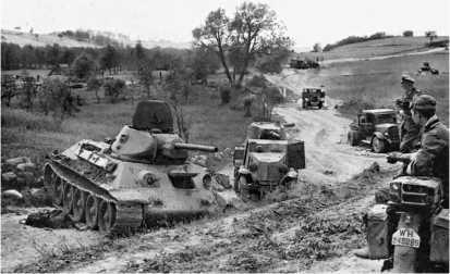 Дорога отступления. Брошенные без видимых повреждений, скорее всего, по причине отсутствия топлива, танк Т-34, бронеавтомобиль БА-10 и грузовики ЗИС-5. Лето 1941 года.