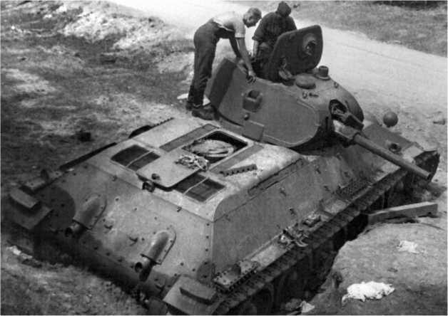 Немецкие солдаты осматривают трофейный танк Т-34. Маска пушки Л-11 сорвана, крышка люка над двигателем откинута и хорошо виден «блин» воздухоочистителя «Помон». Возможно, танк был оставлен экипажем по причине выхода из строя именно воздухоочистителя, что было массовым явлением в 1941 году. Антенный ввод размещен на правом борту корпуса, впрочем, наличие антенного ввода вовсе не свидетельствует о наличии на танке радиостанции.