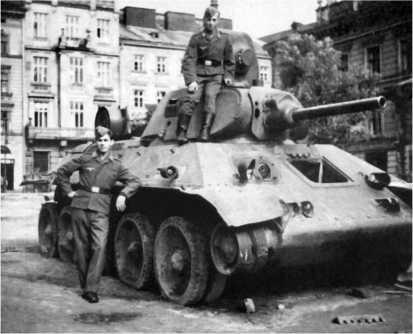 Немецкие солдаты осматривают танк Т-34 с пушкой Л-11, потерявший гусеницу и оставленный экипажем на улице Львова. Июнь 1941 года.