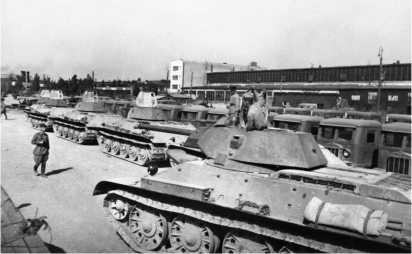 Сдаточная площадка Сталинградского тракторного завода. На переднем плане танки Т-34, на заднем — артиллерийские тягачи СТЗ-5. Июль 1942 года.