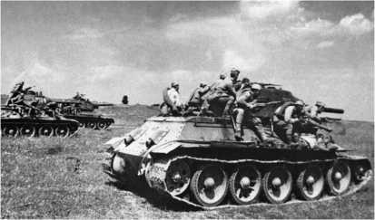 Танк Т-34 с десантом автоматчиков устремляются в атаку. Курская дуга, июль 1943 года. Из-за сильной раскачки удержаться на броне Т-34 в движении было довольно трудно, поэтому пехотинцы часто привязывали себя ремнями к десантным поручням.