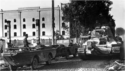 Танк Т-34 с оборудованием для навески каткового минного трала ПТ-3 проходит по одной из улиц Вильнюса. 1944 год.