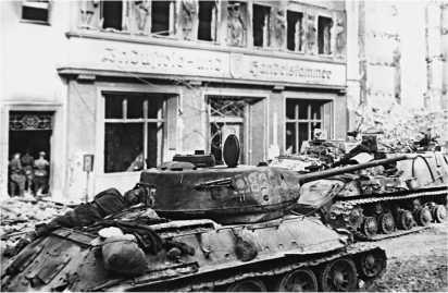 Берлин взят! Танк Т-34-85 и тяжелые САУ И СУ. Вражеским огнем с бортов «тридцатьчетверки» сорвано все, включая наружные баки. За поручнем башни заначен трофейный пистолет-пулемет МР-40.