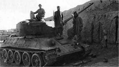Афганские моджахеды осматривают танк Т-34-85, захваченный у формирований Царандоя (внутренних войск). Афганистан, 1982 год.