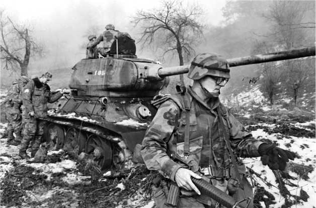 Российские и американские военнослужащие из состава международных сил по поддержанию мира в Боснии осматривают подбитый сербский танк Т-34-85. Босния, 1996 год.