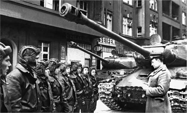 «Наше дело правое, мы — победили!» В одной из танковых частей зачитывается «победный» приказ Верховного главнокомандующего. Берлин, май 1945 года.На переднем плане — И С-2 с корпусом производства УЗТМ.