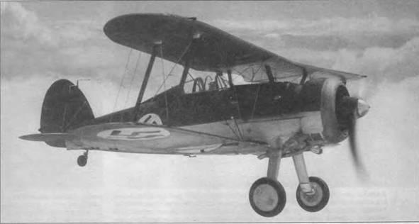 Летчик-испытатель фирмы «Глостер» флайт-лейтенант П.Э.Дж. Сейер совершает пробный полет на «Гладиаторе Mk I» (114), предназначенном для Латвии, середина 1937 года. Самолеты, закупленные Латвией в Англии по морю были доставлены заказчику. Камуфляж самолета Dark Green/Aluminum. Опознавательный знак латвийских ВВС — бордовая свастика на фоне белого круга. Наконечник обтекателя втулки из полированного металла. Латвия стала первой страной, закупившей «Гладиаторы».