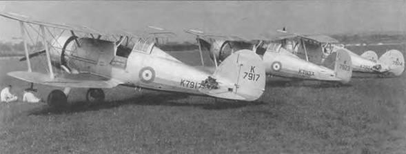 Несколько новых «Гладиаторов Mk I» из 54-й эскадрильи, Хорнчерч, Англия, 1937 год. Два механика беседуют перед ближайшим (K7917) истребителем. У двух самолетов (K7917 и K7924) на хвосте лежат парашют и летный шлем пилота. Бортовые дверцы кабины откинуты, облегчая доступ в кабину. Обычно летчики пользовались только левой дверцей, правую открытии лишь в аварийных случаях.