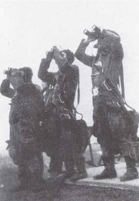 Трое курсантов в полном летном обмундировании внимательно рассматривают в бинокли, как один из их коллег выполняет разворот в воздухе.