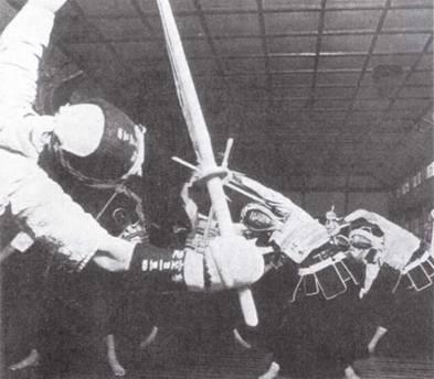 Курсанты Йокарен разминаются перед началам занятий по кендо. Проведение параллелей между Императорскими вооруженмг/ми силами и средневековыми самураями было важной частью обучения и тренировки японских военнослужащих перед Второй мировой войной. (Эдвард М. Йонг)